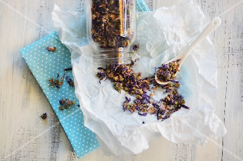 Mallow tea in a glass jar and spread out on paper