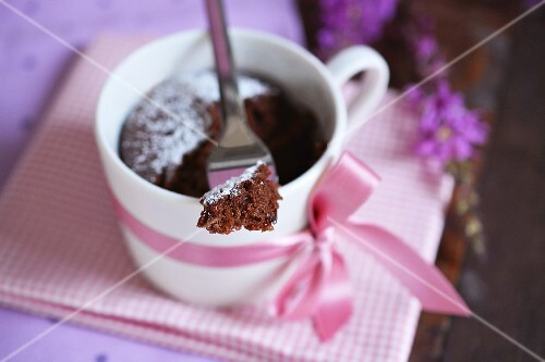 A microwave brownie in a cup decorated with a bow