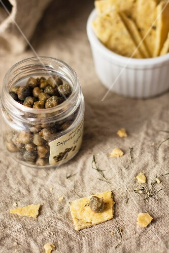 Capers in a glass jar next to crackers
