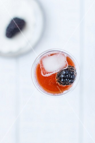 A kir cocktail with a blackberry and an ice cube