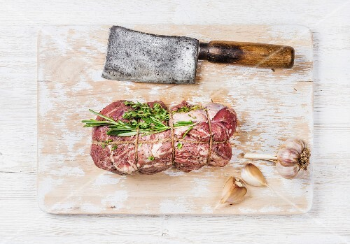 Raw uncooked roastbeef meat cut with rosemary, thyme and garlic and butcher knife on old white painted wooden background