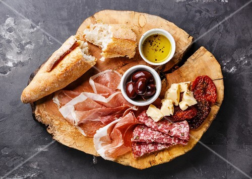 Cold meat plate with prosciutto, salami, bread and olives on wooden board