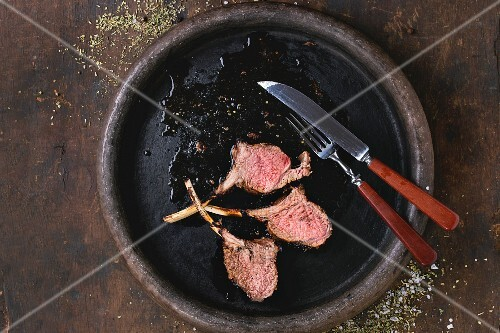 Chopped grilled bbq rack of lamb, served with seasoning, fork and knife on clay tray