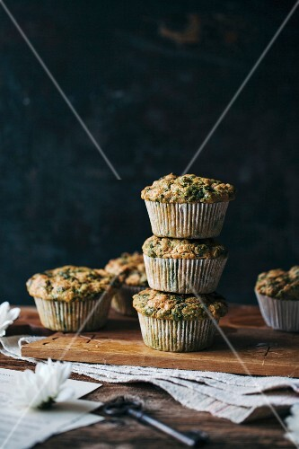 Stack of savoury chard muffins on a wooden board