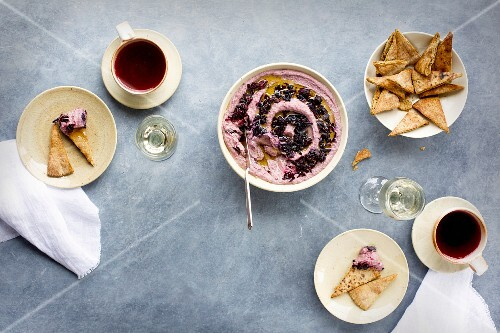 Hibiscus hummus topped with hibiscus flowers and olive oil, served with pita chips