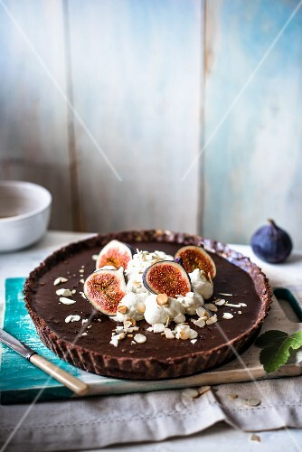 Chocolate tart with cream, fresh figs and almonds