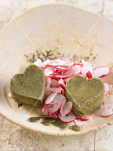 Vegan pumpkin seed and cashew nut cheese hearts with slices of radish