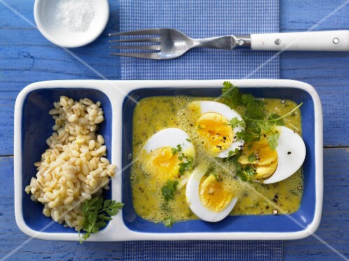 Eggs in curry and mustard sauce with wheat and fresh chervil