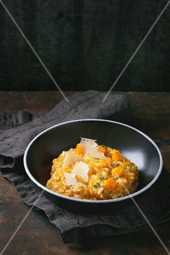 Pumpkin risotto with thyme and cheese on a dark surface