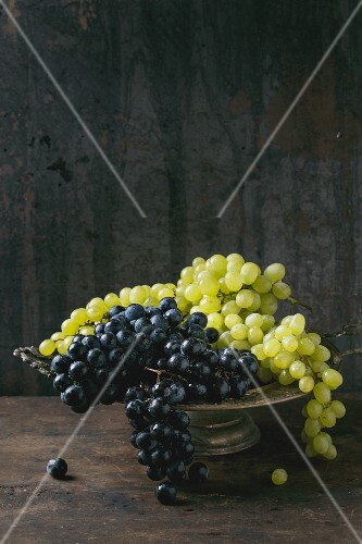 Red and white grapes in an old metal bowl against a wooden background