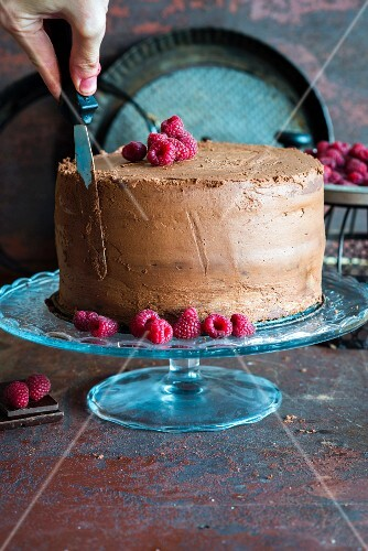 A hand using a spatula to smooth the chocolate cream on the side of a chocolate cake with ganache and raspberries