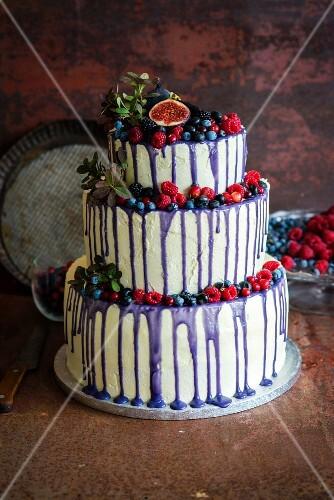 A three-tier wedding cake with forest berries, vanilla buttercream and purple chocolate ganache