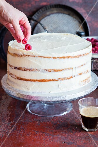 A vanilla layer cake being decorated with raspberries