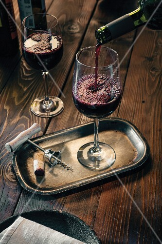 Red wine being poured into a glass on a metal tray with a corksrew and cork