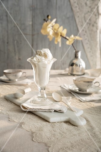 A vanila ice cream sundae on a vintage table with a lace tablecloth and white orchid