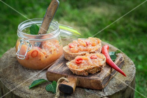Bread topped with apple and chilli jam on a wooden board in the garden