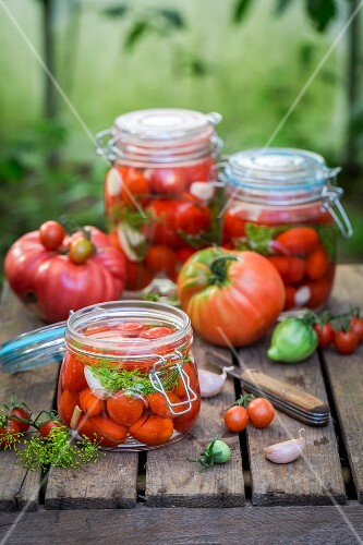 Preserved and fresh tomatoes with ingredients on a wooden crate in the garden