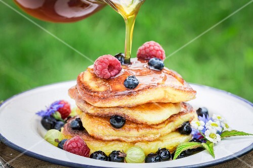 Maple syrup being drizzled onto a pile of pancakes with fresh berries