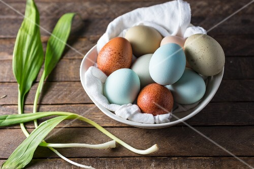 Colourful eggs in a bowl next to fresh ramp