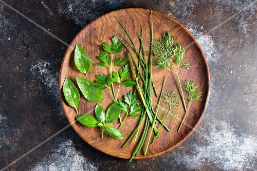Assorted fresh herbs on a wooden plate