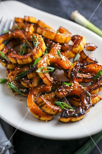 Roasted pumpkin wedges with spring onions and sesame seeds