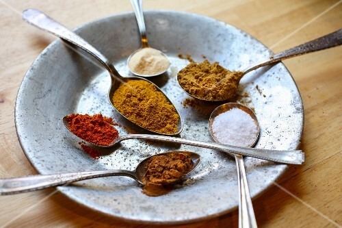 Several spoons containing spices on a metal plate