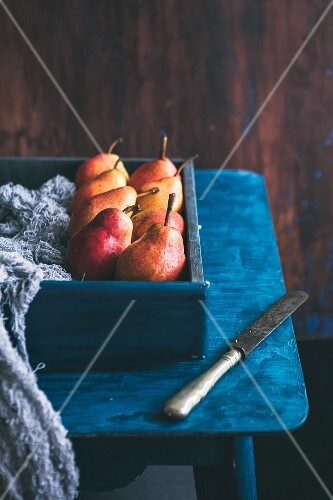 Pears in a wooden box on a blue cloth