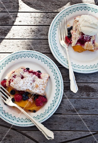 Raspberry, blueberry and peach cobbler on plates