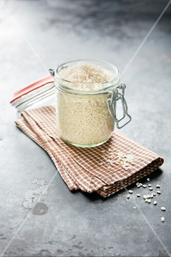 Short-grain rice for rice pudding in a preserving jar on a tea towel