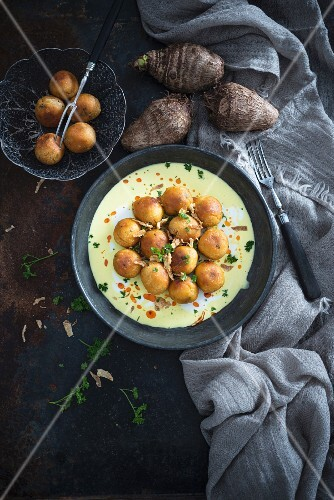 Deep-fried taro balls with coconut and curry sauce and fried onions (vegan)