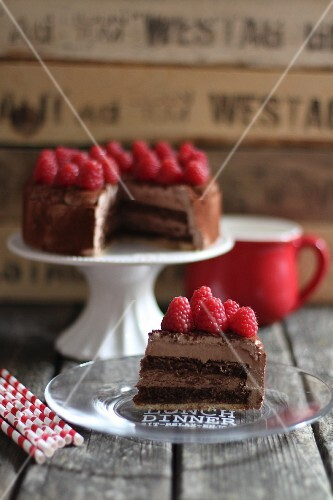 Sliced chocolate cake with raspberries on a cake stand and plate