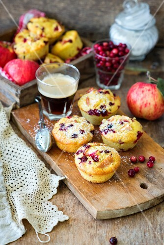 Apple and cranberry muffins on a wooden board