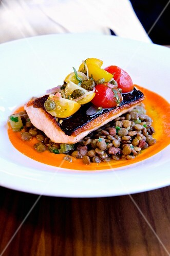 Pan-fried fillet of salmon on a bed of lentils with dried tomato jus and cherry tomato salsa