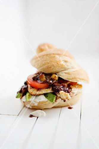 A chicken sandwich with avocado and tomato