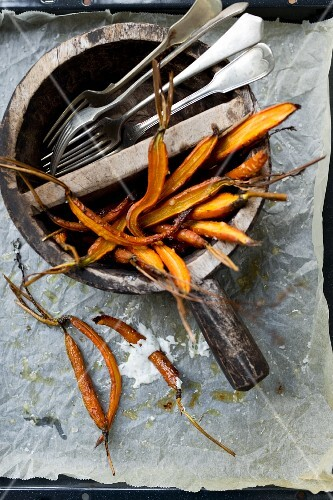 Baked carrots in a wooden bowl with cutlery