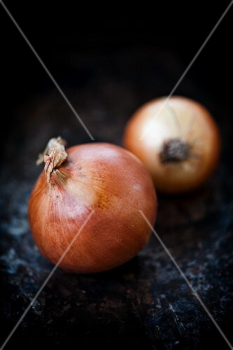 Two onions on a dark surface