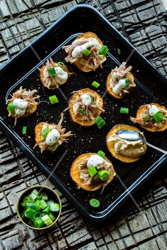 Sweet potato rounds with hummus, pulled pork, spring onions and sour cream