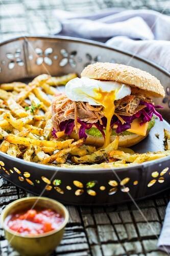A burger with pulled pork, Cheddar, avocado cream, a poached egg and celeriac chips