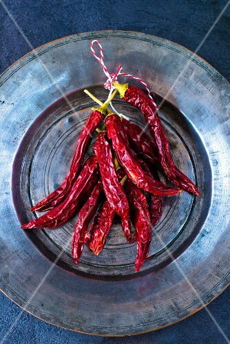 A bunch of dried red Indian chilli peppers on a Persian tin plate