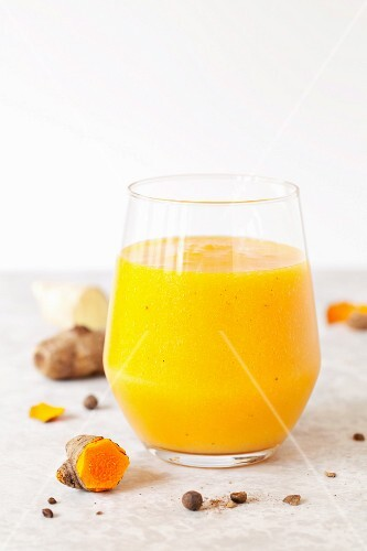 A glass of mango and pineapple smoothie with turmeric