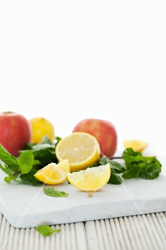 Apples, lemon and mint on a chopping board
