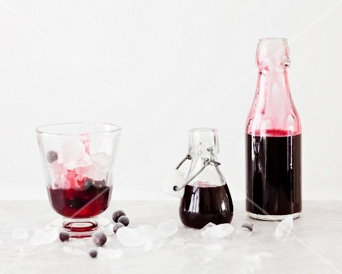 Blackcurrant syrup with vanilla in a glass and bottles