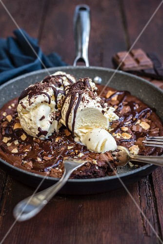 A brownie with vanilla ice cream in a frying pan