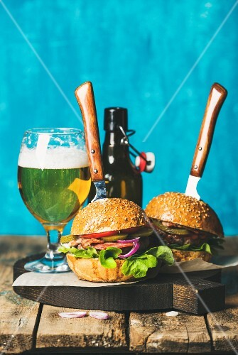Two homemade beef burgers with crispy bacon, onion, pickles, vegetables, glass and bottle of wheat beer