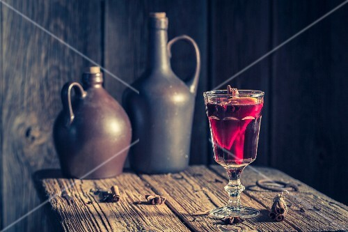 A glas of mulled wine with spices on a rustic table for Christmas