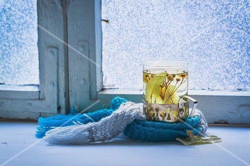 Hot tea with herbs by a window