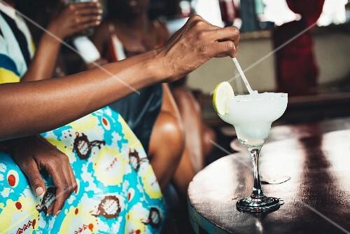 Dunkelhäutige Personen mit Cocktail im Restaurant Potato Shed (Johannesburg, Südafrika)
