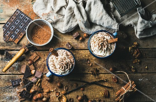 Hot chocolate with whipped cream, nuts and cinnamon in enamel mugs with ingredients on a rustic wooden surface