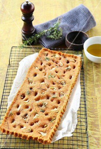 Vegan focaccia with dried tomatoes, garlic and herbs on a cooling rack