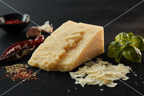 A wedge of Asiago cheese, basil and spices on slate
